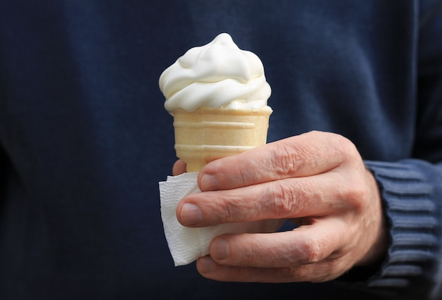 Cone de gelado branco que derrete na mão de um homem, mão em uma camisola longa da luva.