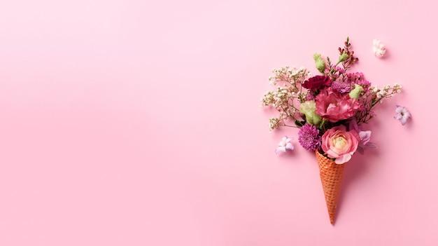 Cone de gelado com flores cor-de-rosa e folhas no fundo pastel punchy.