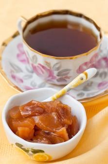 Cone de marmelo hommade e xícara de chá em fundo amarelo
