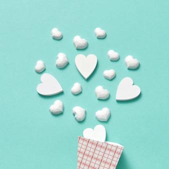 Cone de papel com pequenos corações de gesso branco como sobremesa doce de sorvete