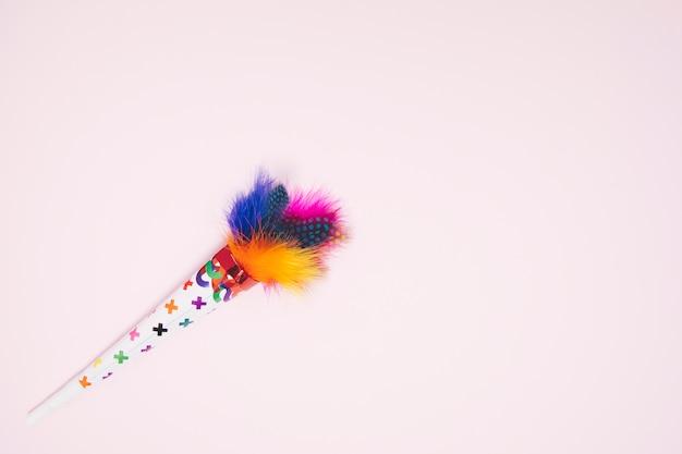 Cone de penas decorativas coloridas contra fundo rosa