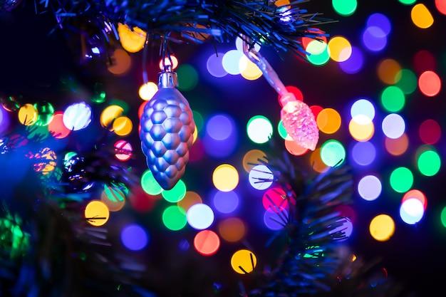 Cone de prata bola de natal pendurado em uma árvore de natal no fundo muito guirlandas brilhando em cores diferentes.