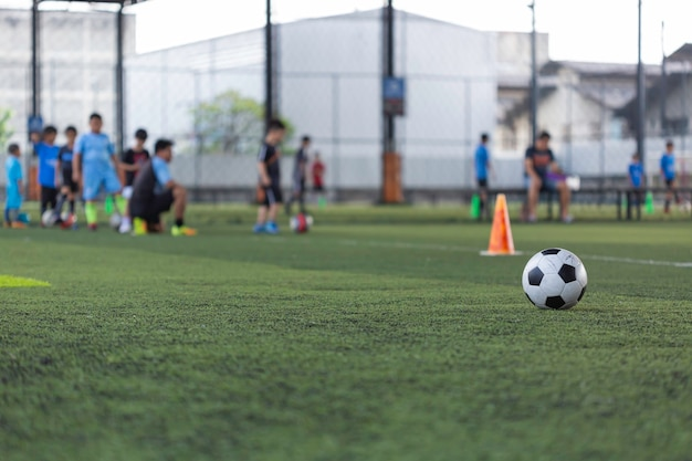 Cone de táticas de bola de futebol no campo de grama com fundo de treinamento.