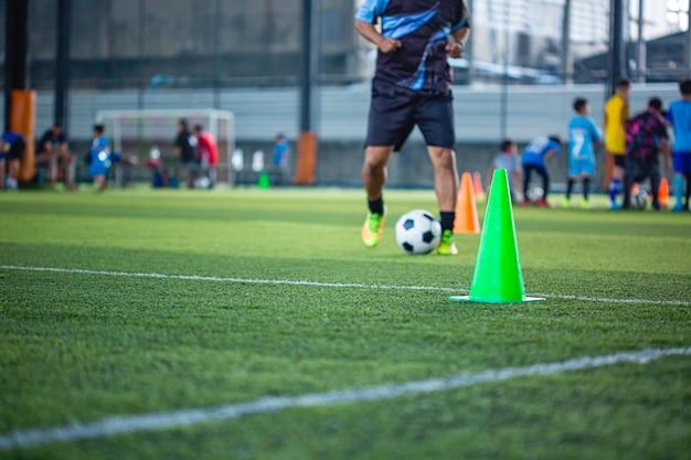 Cone de táticas de bola de futebol no campo de grama com fundo de treinamento
