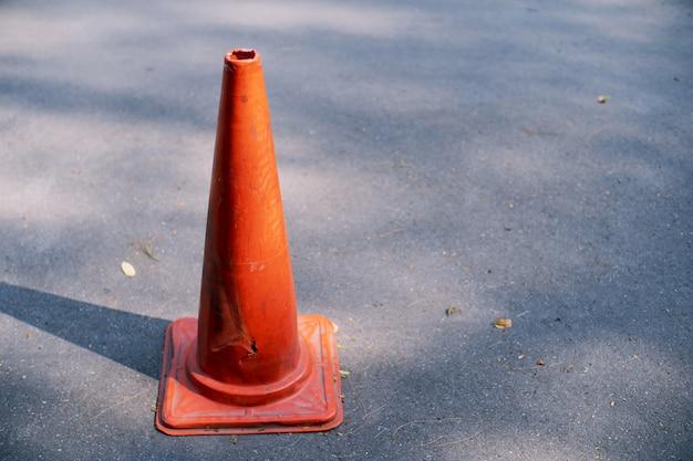 Cone de tráfego antigo na estrada fundo close-up