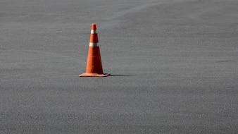 Cone de tráfego laranja velho na estrada de asfalto