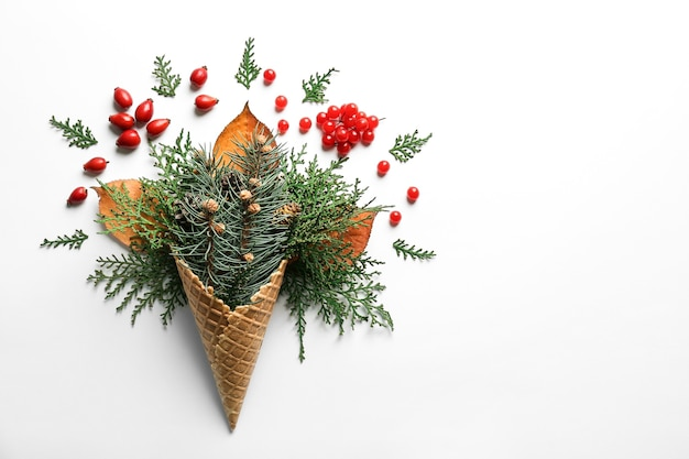 Cone de waffle com composição de ramos de coníferas, bagas e estróbilos em fundo branco