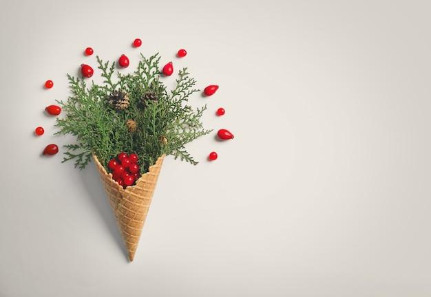 Cone de waffle com composição de ramos de coníferas, bagas e estróbilos