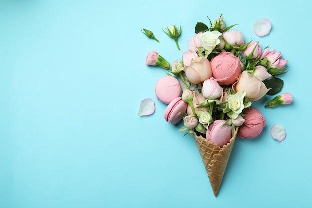 Cone de waffle com flores, bolas de sorvete e biscoitos no fundo azul