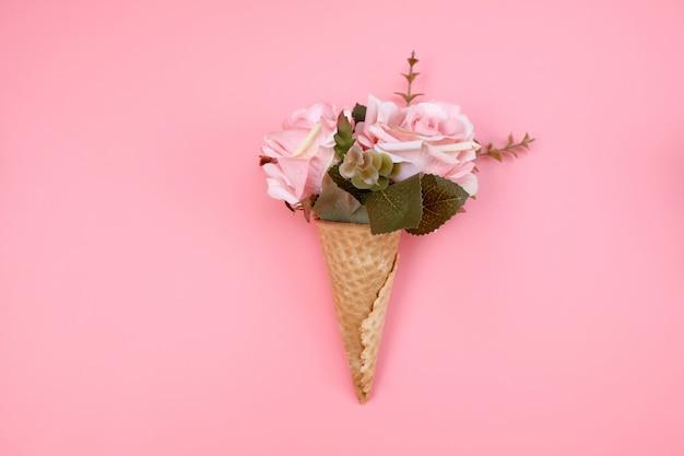 Cone de waffle com flores sobre fundo rosa. decorações de aniversário, aniversário, casamento. conceito mínimo de férias decorativas.