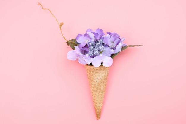 Cone de waffle com flores sobre fundo rosa