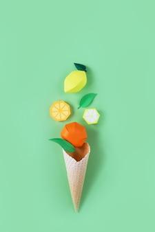 Cone de waffle com frutas de papel na superfície verde