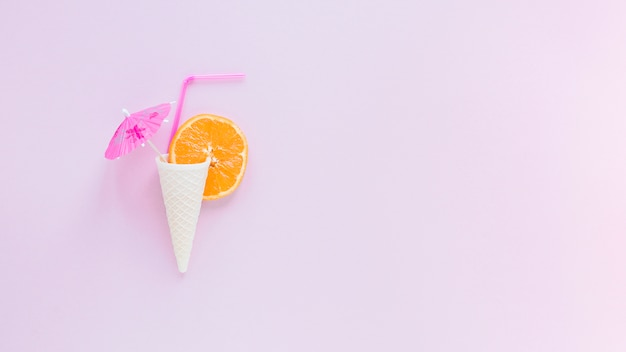 Cone de waffle com laranja, palha e guarda-chuva