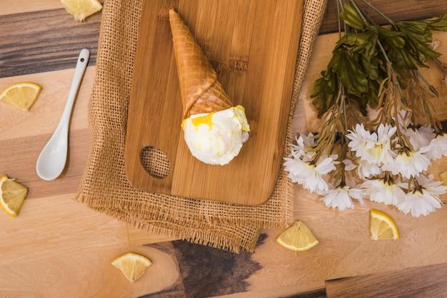 Cone de waffle com sorvete a bordo perto de fatias de frutas frescas e flores
