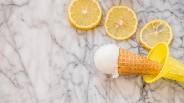 Cone de waffle com sorvete perto de fatias de frutas frescas