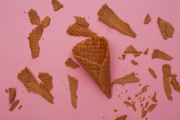 Cone de waffle destruído em fundo rosa pastel.
