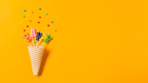 Cone de waffle no texto feliz velas com granulado no pano de fundo amarelo