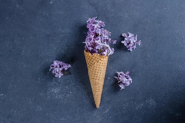 Cone do waffle com lilás roxo na obscuridade - fundo concreto da tabela da pedra azul. vista plana, topo