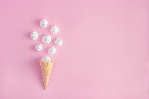 Cone do waffle e merengues torcidos brancos no fundo cor-de-rosa