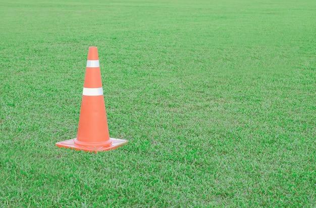 Cone ou funil do tráfego no fundo verde do campo.