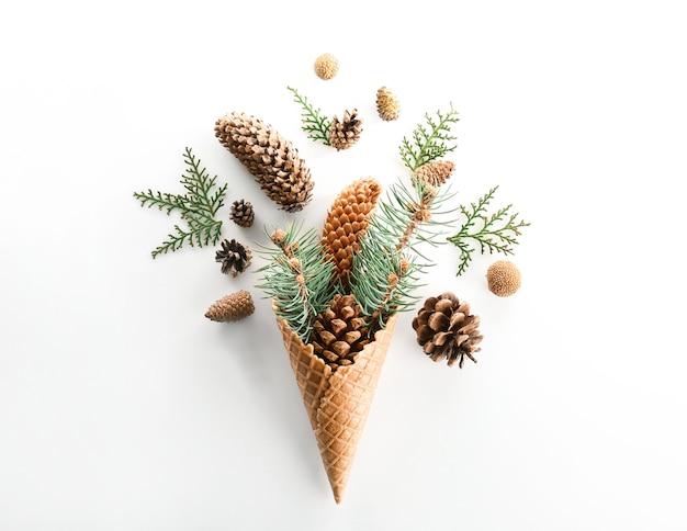 Cone waffle com galhos coníferos e estróbilos em fundo branco