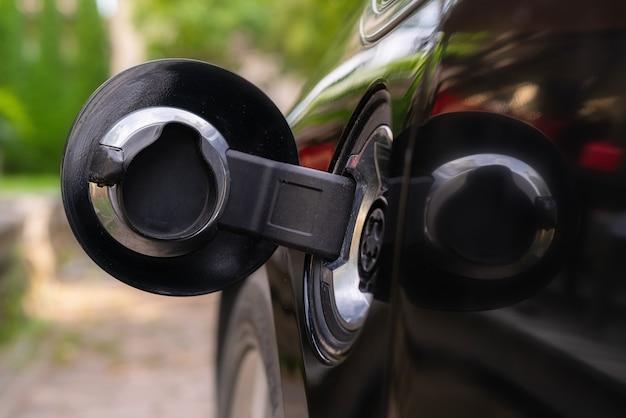 Conecte o carregador em um carro elétrico em uma superfície de ambiente verde.