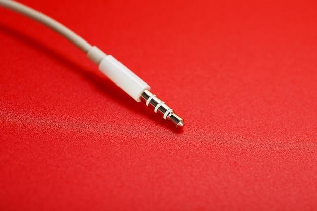 Conector branco cabo branco aux em um fundo vermelho