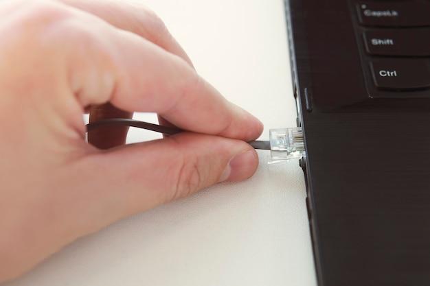 Conector de plugue do cabo ethernet no conceito de tecnologia de teclado de computador portátil. mão segure o close up do cabo de rede. patch cord de conexão para laptop rj45