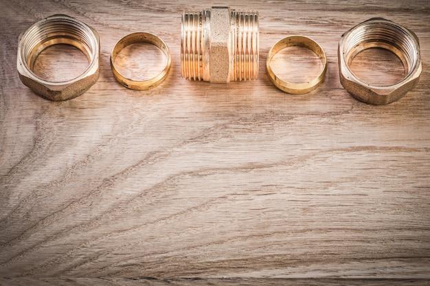 Conectores de mangueira de mamilo com rosca de latão no conceito de encanamento de placa de madeira