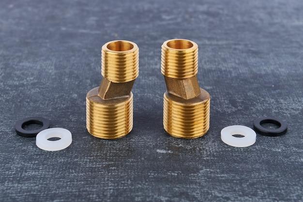 Conectores excêntricos de latão para o close up da instalação da torneira do misturador de água da parede em um fundo cinza, profundidade rasa de nitidez