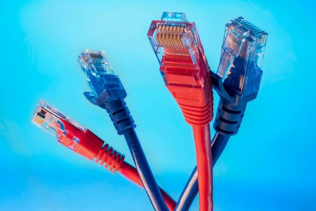 Conectores vermelhos e azuis para a internet, duas cores de fios de dados em um fundo azul