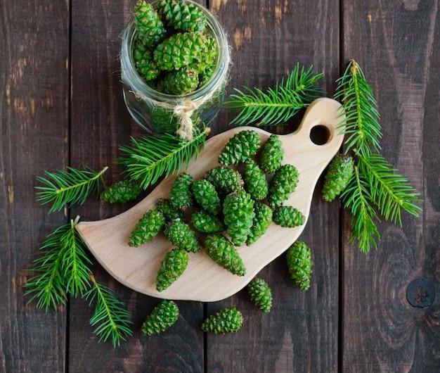 Cones de abeto verdes jovens na mesa de madeira. para fazer infusão medicinal.