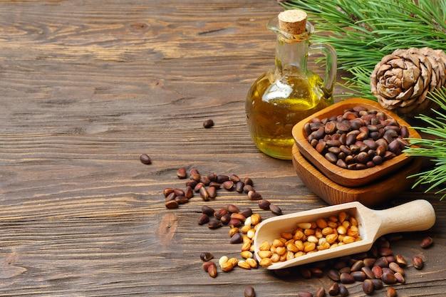 Cones de cedro, nozes e óleo de noz de cedro em uma garrafa transparente sobre uma mesa de madeira