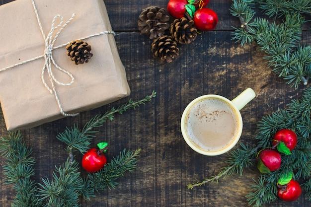 Cones de coníferas e maçãs falsas perto de presentes e café