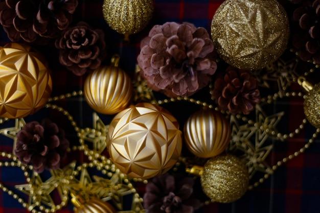 Cones de decorações de natal e bolas douradas sobre o fundo xadrez azul-vermelho. ano novo plano estabelece.