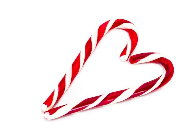 Cones de doces de natal formando um coração e isolado em um fundo branco.
