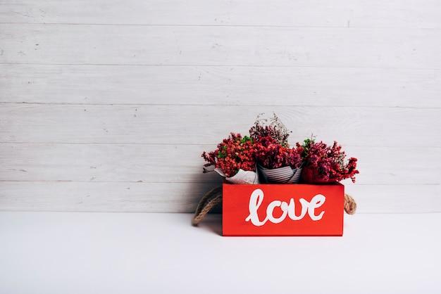 Cones de flores na caixa de amor na mesa branca contra o pano de fundo de madeira