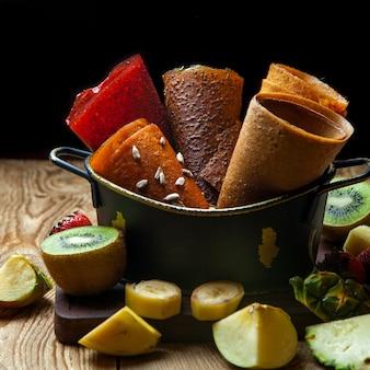 Cones de frutas pastila na cesta com frutas frescas