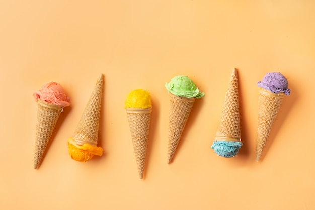 Cones de gelado coloridos no backgound amarelo. conceito de verão