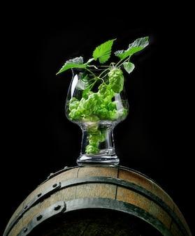 Cones de planta de lúpulo fresco em copo de cerveja artesanal em um velho barril de madeira