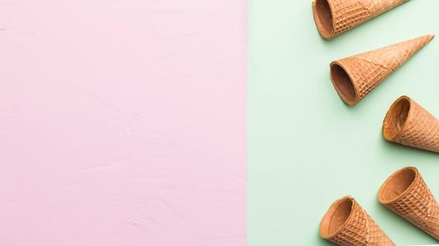 Cones de sorvete saborosos vazios na superfície multicolorida