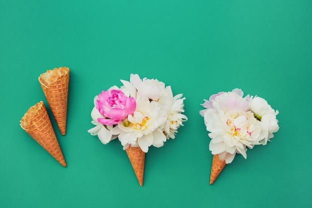 Cones de sorvete waffle com flores de peônia branca em verde