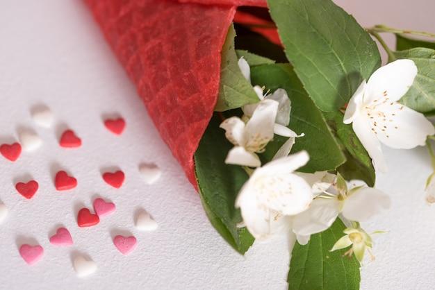 Cones de sorvete waffle com peônia branca flores sobre fundo vermelho. conceito de verão. copie o espaço, vista superior. minimalismo