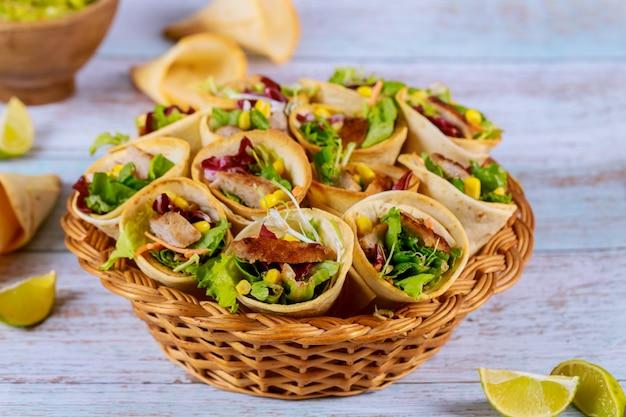 Cones de tortilhas assadas com alface e carne na superfície de madeira