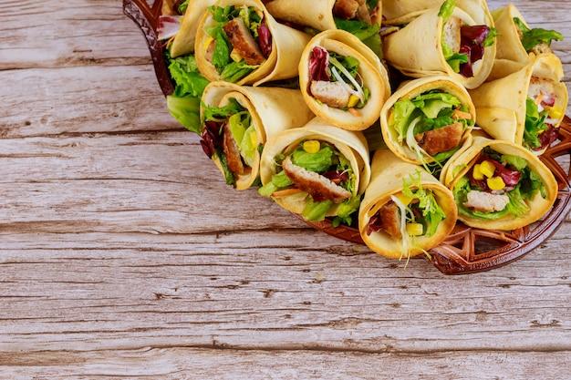 Cones de tortilhas mexicanas cheias de carne, milho e salada na mesa de madeira.