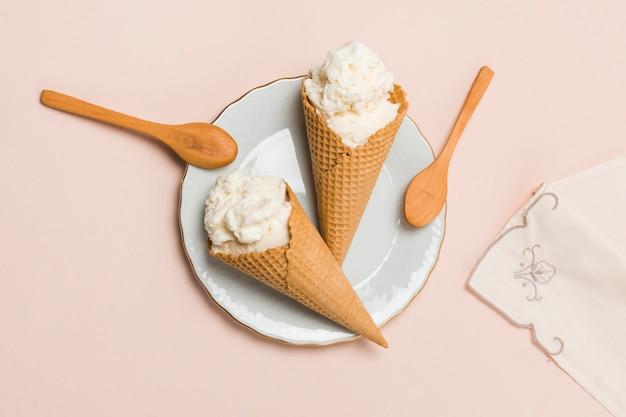 Cones de waffle com sorvete e colheres na placa