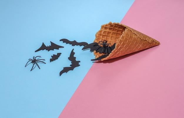 Cones de waffle de sorvete com morcegos decorativos e aranhas em fundo pastel brilhante rosa e azul com sombra profunda. composição de halloween