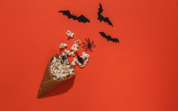 Cones de waffle de sorvete com morcegos decorativos e aranhas, pipoca em fundo laranja brilhante. vista do topo. filme assustador. composição plana de halloween
