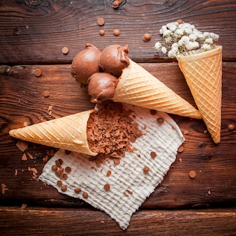 Cones de waffle de vista superior com sorvete de chocolate e gypsophila e lascas de chocolate em guardanapos de pano