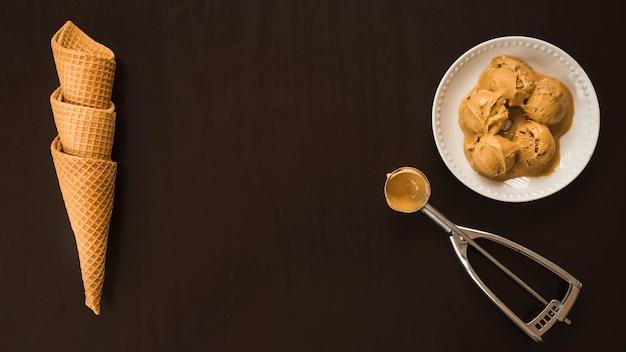 Cones de waffle perto de bolas de sorvete no prato e colher